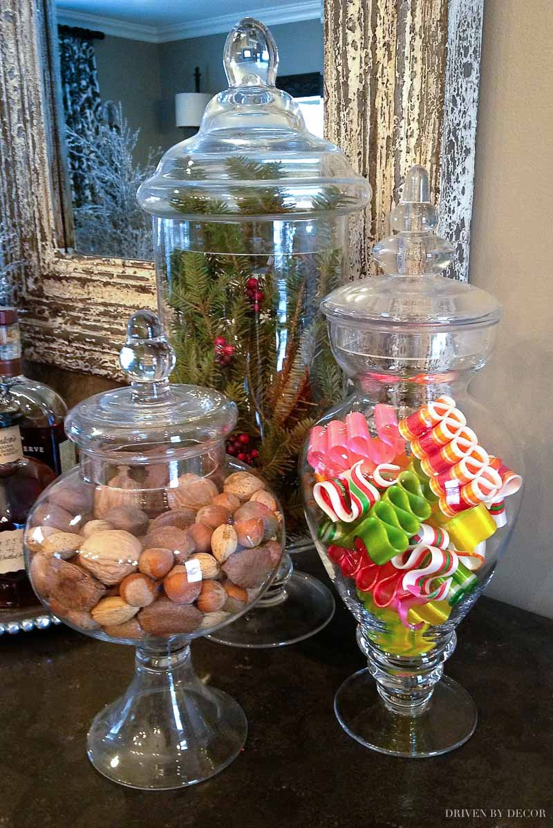 Apothecary jars filled with nuts, ribbon candy, and greenery for Christmas!