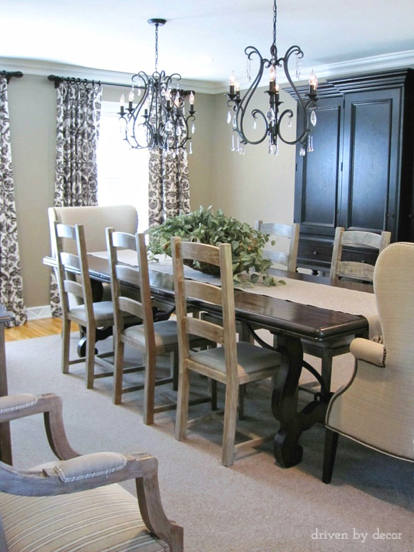 Dining room with twin chandeliers, wingback end chairs, and taupey gray walls