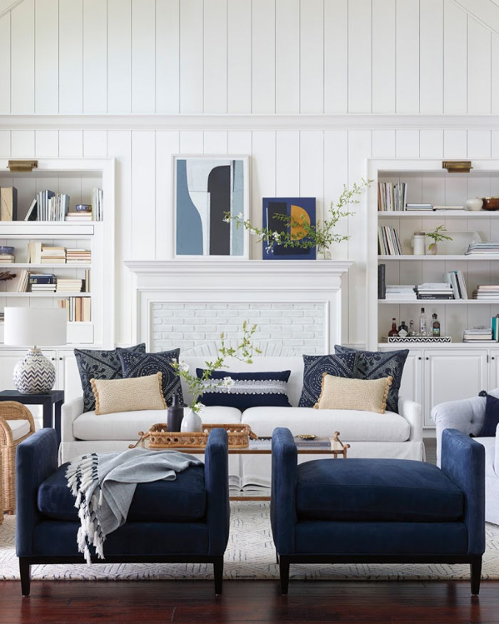 Indigo pillows and ottomans add pops of color in this gorgeously decorated living room!