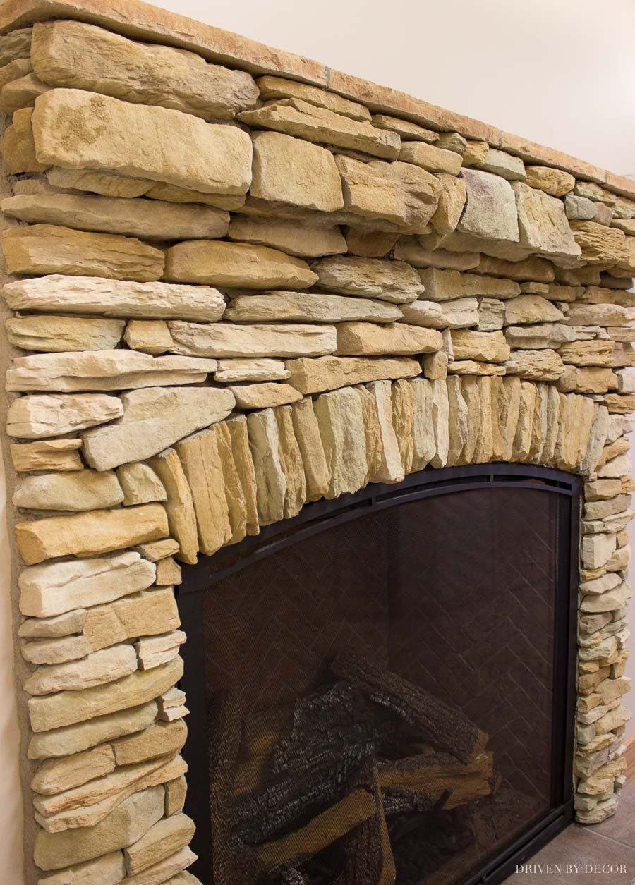 Loving the arched stone accent on this stone veneer fireplace
