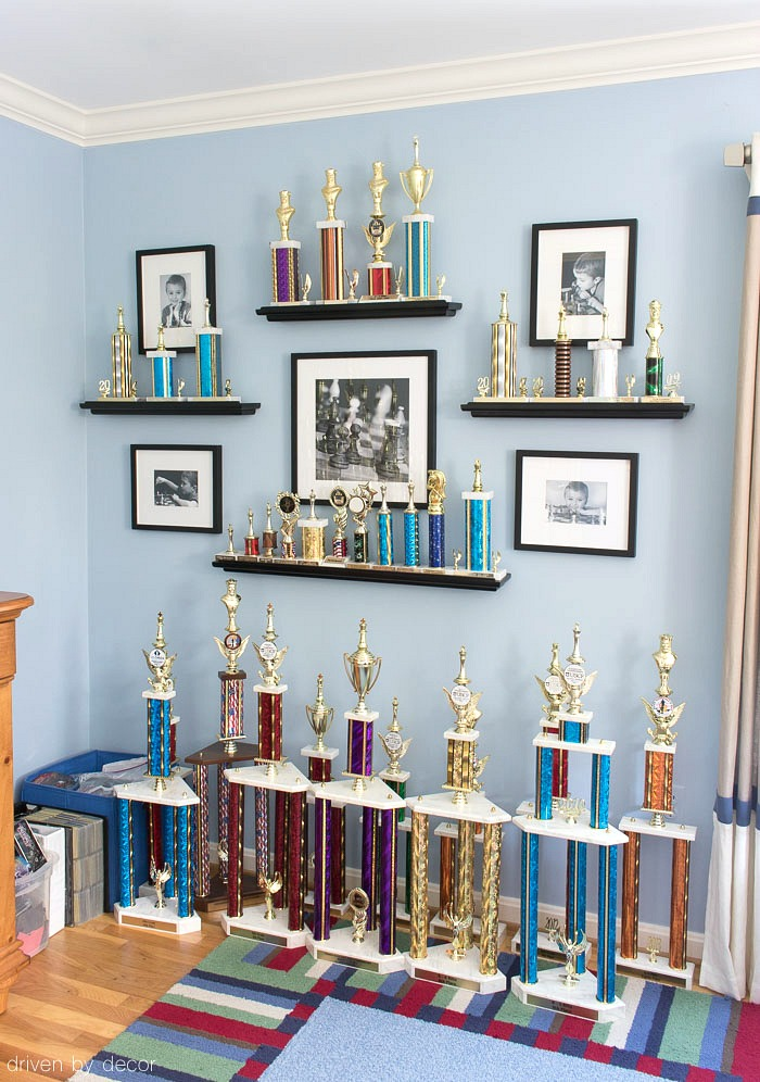 LOVE this idea for displaying kids trophies and awards on the wall - trophies sit on open shelves with black and white framed photos surrounding them