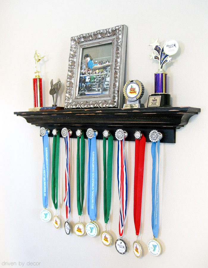 Such a cute way to display your kid's trophies and medals - shelving for the trophies and knobs for medals!