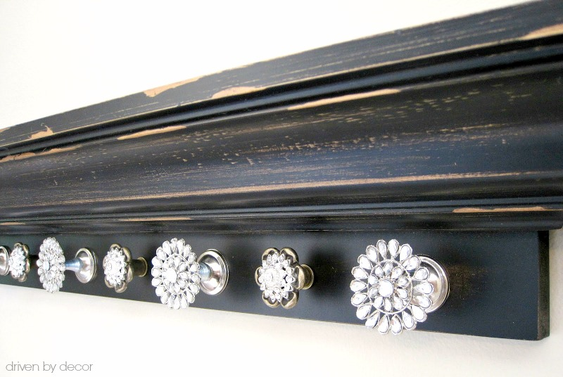 Rhinestone knobs added to a wall-mounted ledge shelf to create an awards medal display