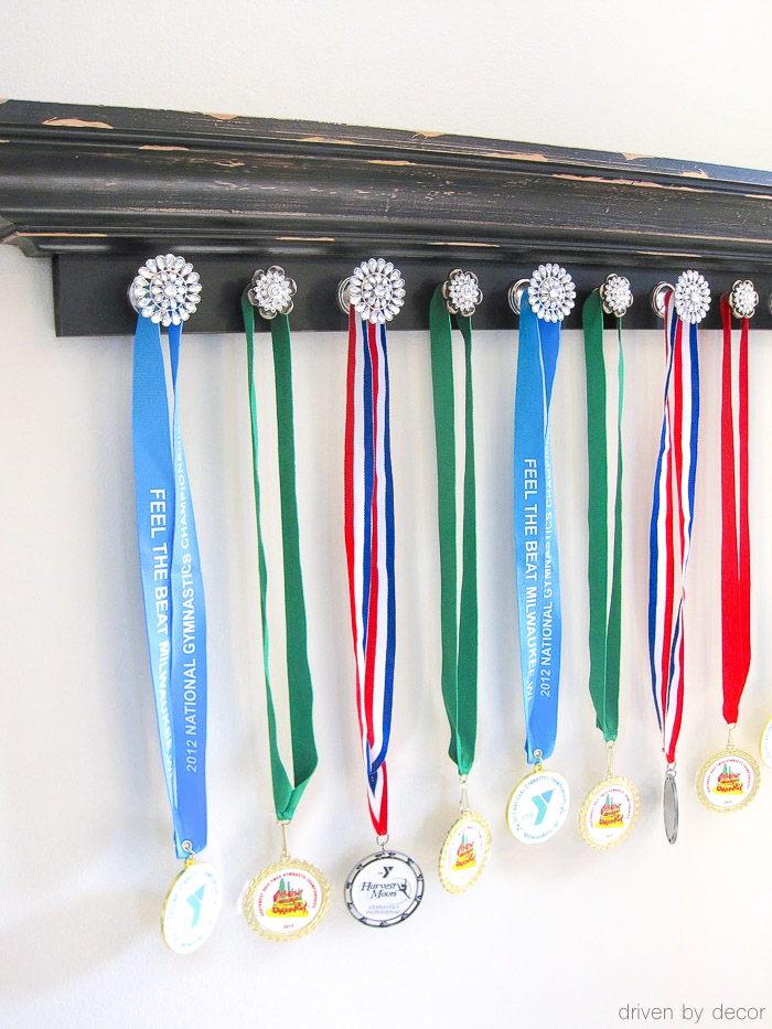 Ledge shelf with knobs attached to hold sports medals - love this idea!