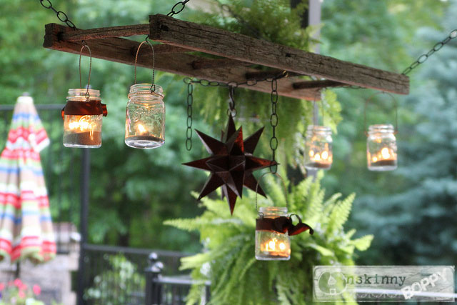 Mason jar candles hung from ladder suspended above table