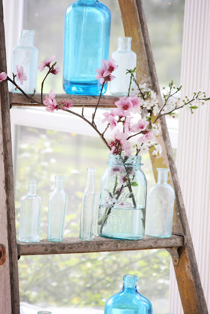 Sea colored bottles on vintage ladder