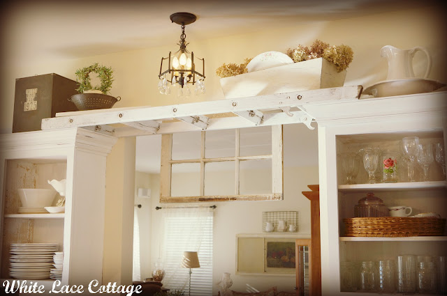 Vintage ladder spans kitchen cabinet to create a unique spot to display accessories