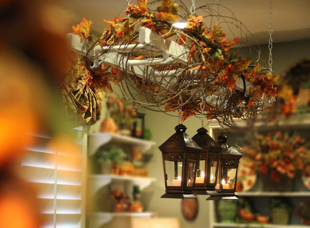 Vintage ladder suspended over table with leaves and lanterns hanging from it - beautiful!