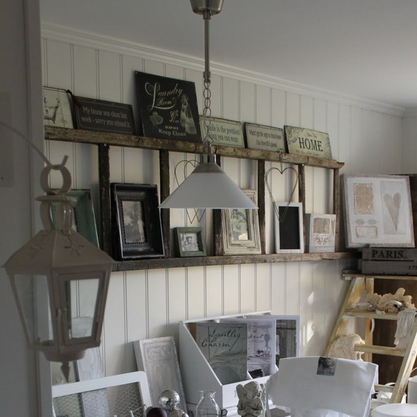 Vintage ladder used to display framed photos and art