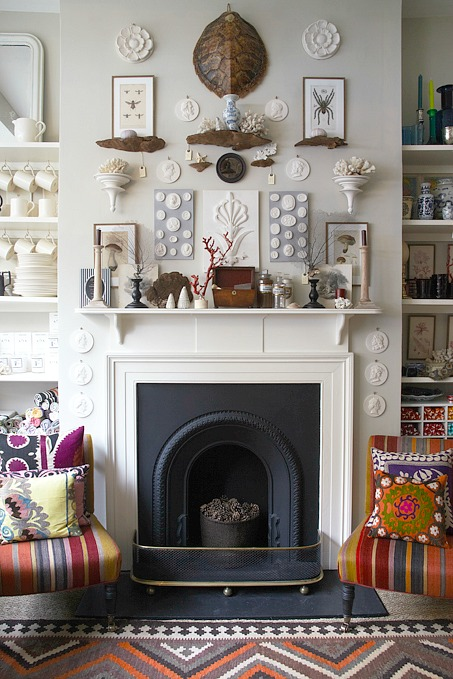 Faux turtle shell used as part of an eclectic collection of art over a fireplace mantel
