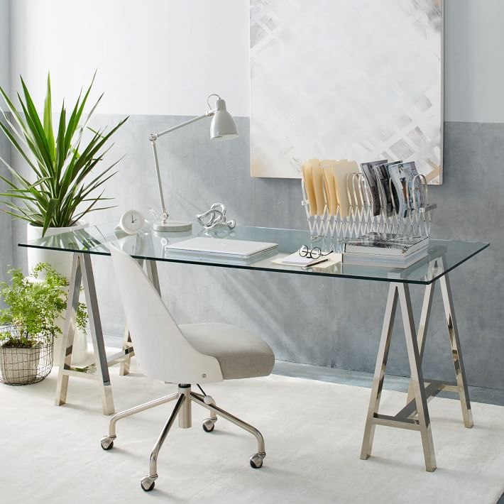 A stunning glass desk with polished nickel sawhorse legs