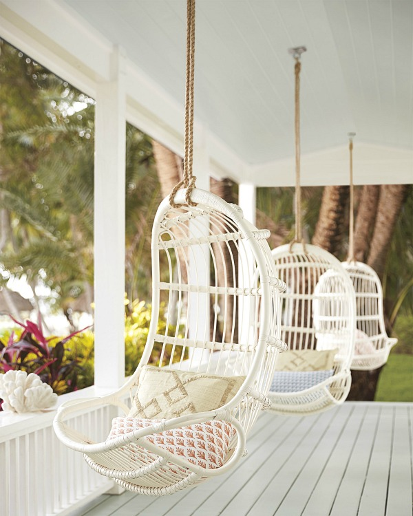 Porch lined with hanging rattan chairs - so dreamy!