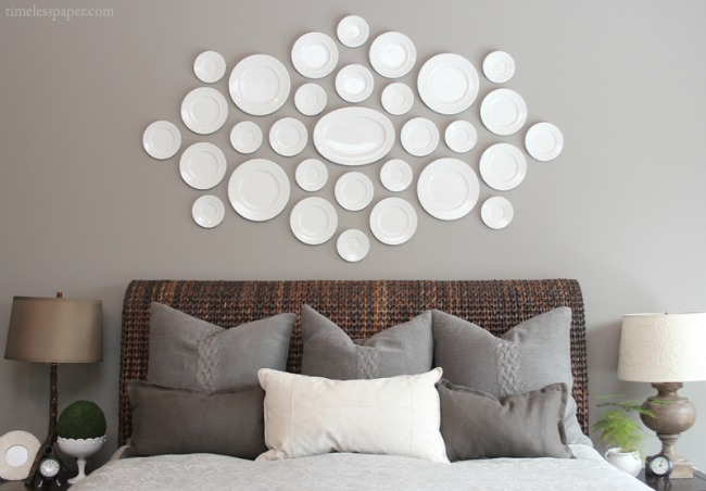 A collection of plates hung over the bed is a beautiful way to fill that awkward space!