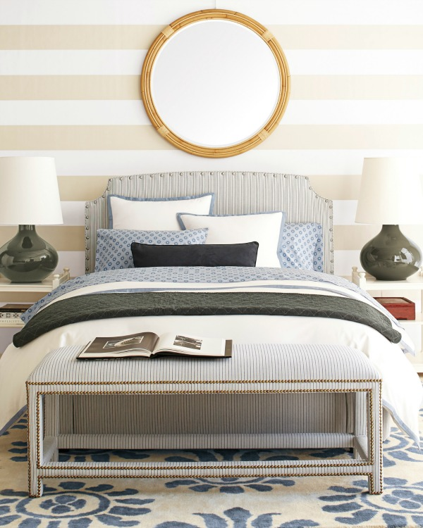 A single round mirror is a great choice for filling the space above your bed