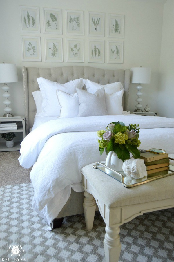 Beautiful guest bedroom retreat with art hung in grid above the bed - Kelley Nan