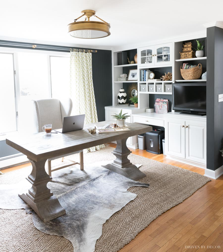 Love the layered cowhide look of a light cowhide layered over a jute rug in this home office