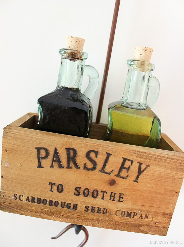 This cute hanging wooden herb box is perfect for holding tabletop essentials like oil and vinegar bottles!