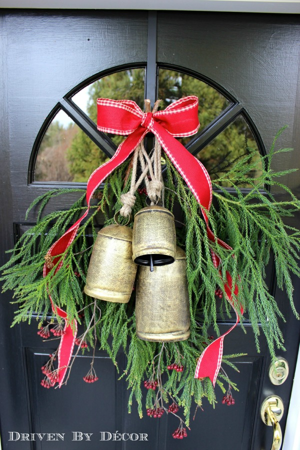 Simple holiday door decoration with greenery and bells