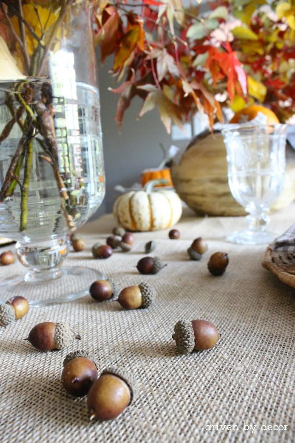 Driven by Decor - Acorns scattered across Thanksgiving table runner