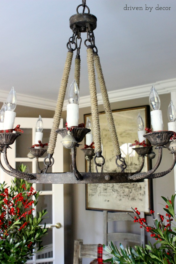 Chandelier dressed up for the holidays with jingle bells tied on with ribbon