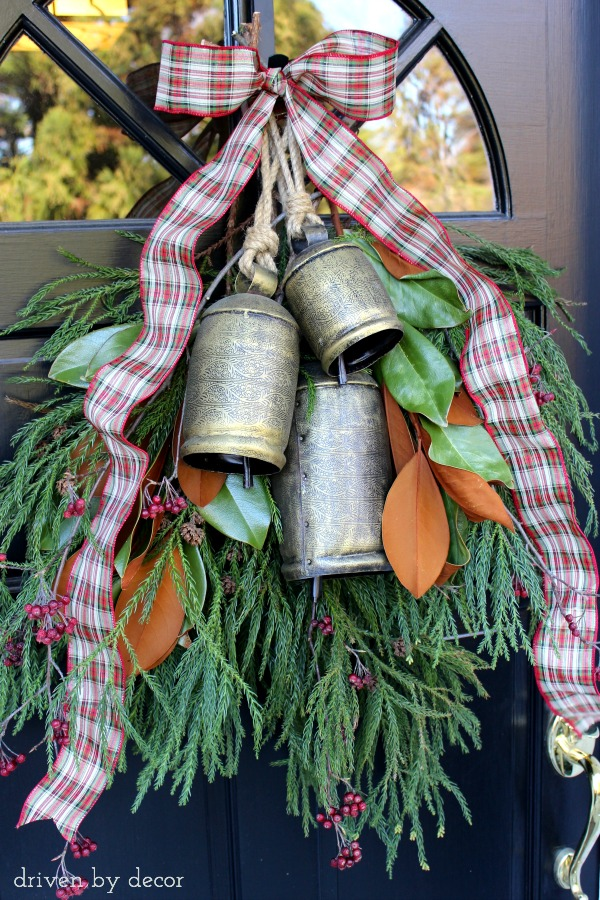 A swag of fresh greenery and large bells make this a welcoming holiday door decoration