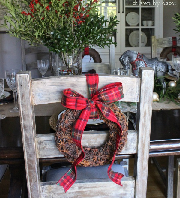 Star anise wreaths hung with plaid ribbon on the backs of dining room chairs - love this for Christmas!