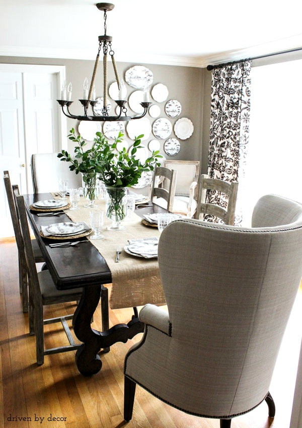 Dining room decorated in neutrals - wingback end chair, ladderback side chairs, rope chandelier, and statement-making plate wall!