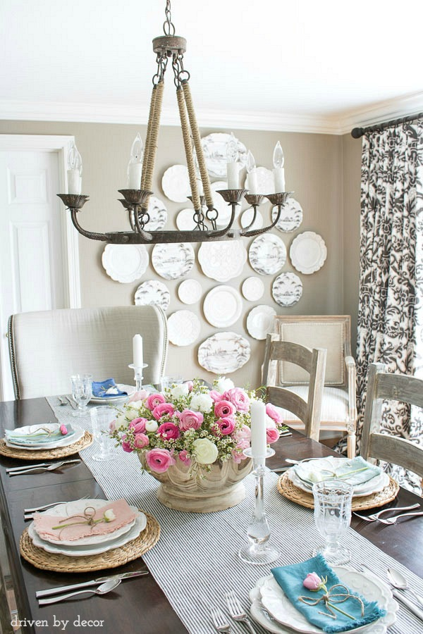 Spring dining room - love the simple centerpiece of a scalloped wood bowl filled with flowers. And the colorful napkins with a single flower on each plate is perfect!