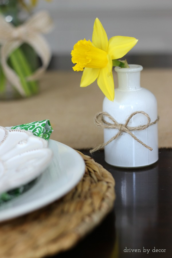 A single cut daffodil in a small vase next to each spring table placesetting