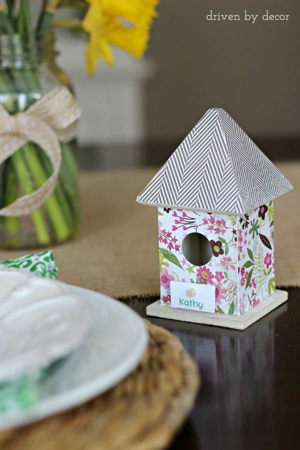 Dollar bin birdhouse covered with scrapbook paper holds name card for Easter table