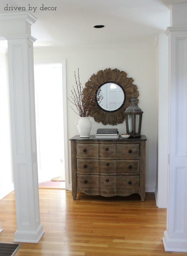 Foyer with weathered chest and round wood and iron mirror