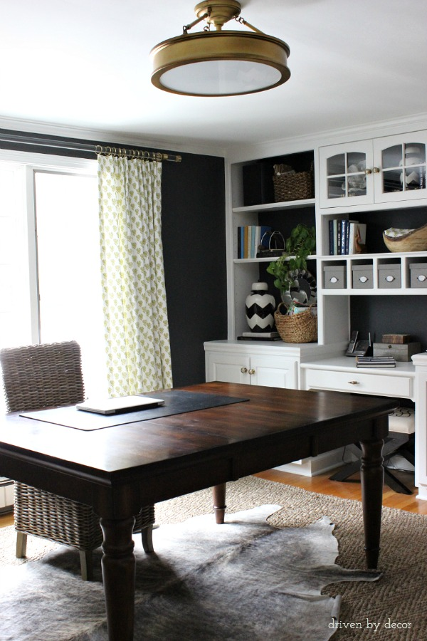 Home office: Black walls || lucite and brass drapery rods || brass flush mount light || white built-ins