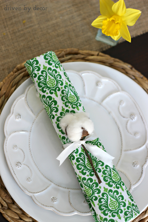 Simple spring place setting with cotton stem tied onto rolled napkin