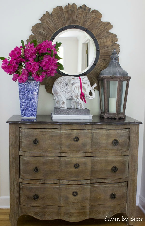 Beautiful round wood mirror over foyer chest