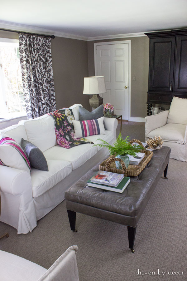 Family room with neutral base and pops of color added in pillows and throw