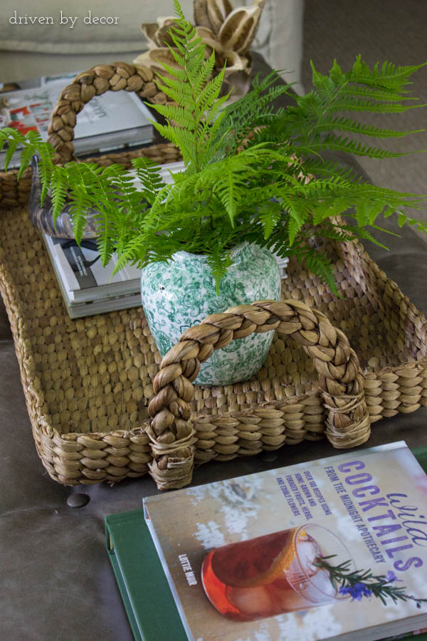 Large woven tray, books, and a plant decorate a rectangular ottoman