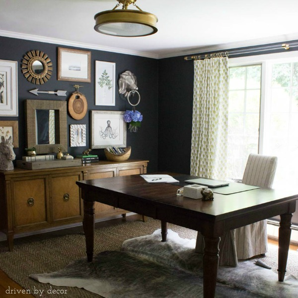 Home office with dark charcoal walls and eclectic gallery wall