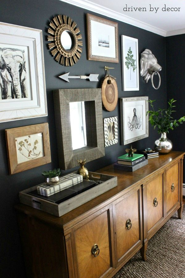 Eclectic gallery wall on dark charcoal wall