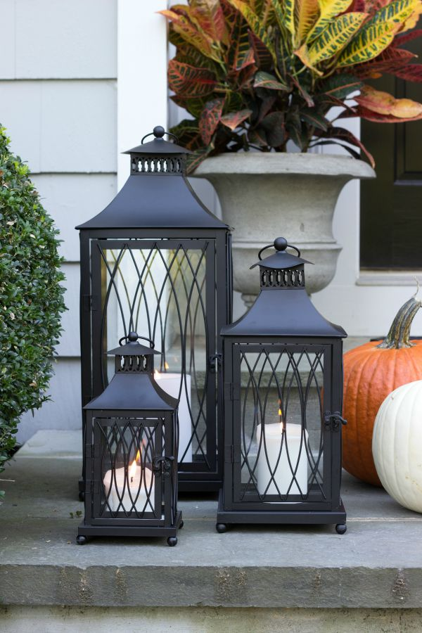 Create a festive fall porch with candle-lit lanterns, pumpkins, and colorful croton plants