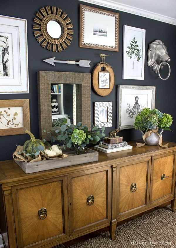 eclectic gallery wall on dark charcoal walls console decorated with