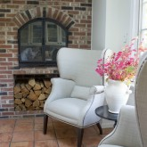 Two chair seating area next to brick kitchen fireplace