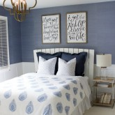 Modern coastal bedroom makeover with quatrefoil chandelier, grasscloth wallpaper, wood and chrome nightstand, and blue and white bedding - beautiful!