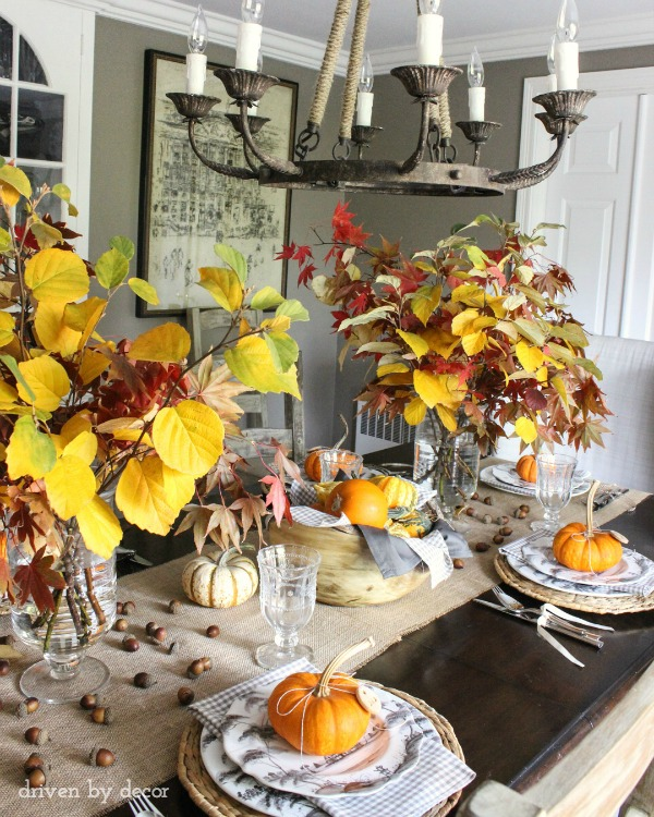 Thanksgiving tablescape with fall branches in glass hurricane vases