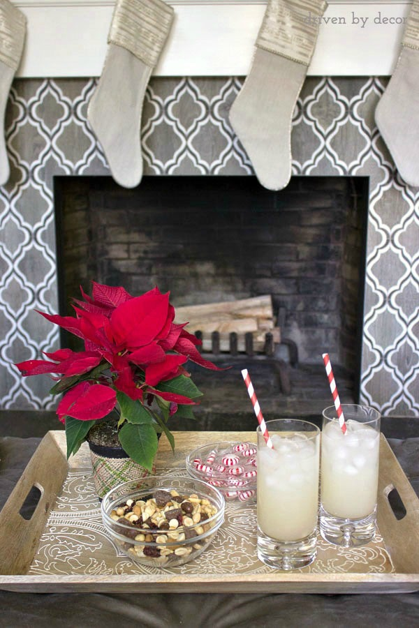 A decorative wood tray on a family room ottoman corrals holiday drinks and snacks