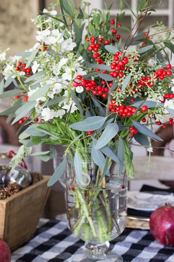 A mix of white flowers, red berries, and eucalyptus make up this festive holiday table floral centerpiece