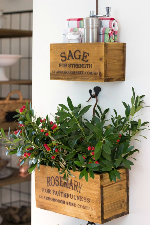 A set of nesting herb crates hanging on the kitchen wall hold greenery along with tabletop necessities