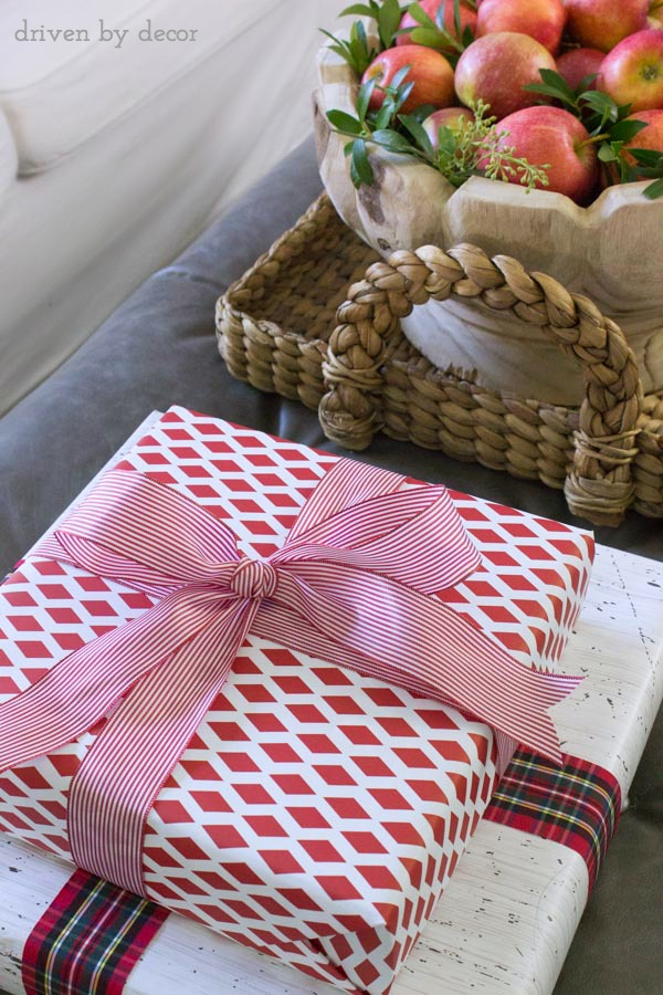 A stack of wrapped presents on an ottoman for holiday decor