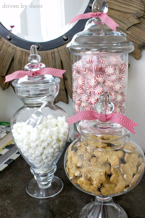 Apothecary jars filled with mints, mini marshmallows, and gingerbread men for the holidays