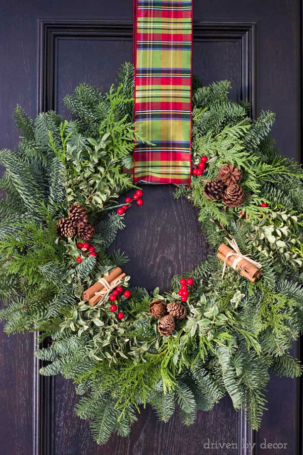 Beautiful holiday wreath made with greenery, pinecones, berries, and bundles of cinnamon sticks