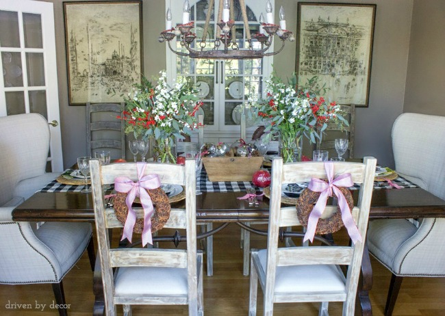 Dining room decorated for the holidays with a centerpiece of flowers and ornaments, star anise wreaths tied to the chair backs, jingle bells on chandelier, and pomegranate place cards